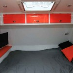 Overhead storage cupboards surround the bedroom and the under-bed storage