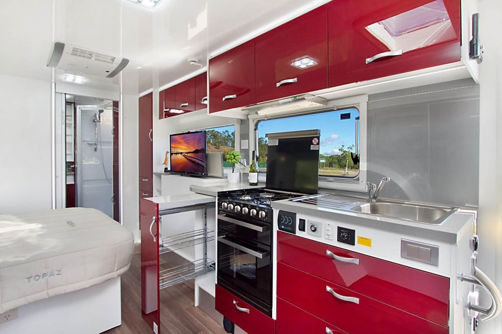The kitchen in the CV7652SL Topaz caravan isn't short of storage space. There's plenty of overhead storage, drawers and also a clever pull out pantry. This caravan has been optioned with Ruby Super Gloss panels, Amaretto Stone benchtops and the Steel coloured splashback.