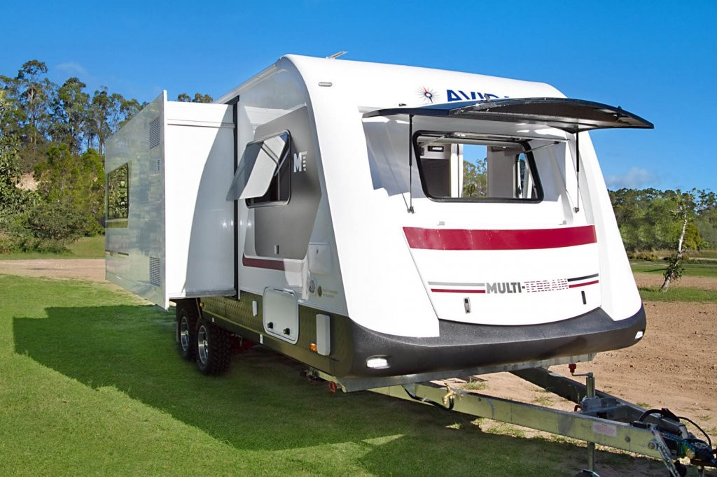 This is the CV7652SL Topaz caravan with Multi Terrain pack. It is parked up with the slideout room open. It has Arctic White coloured fibreglass walls with Maroon Haze coloured decals.