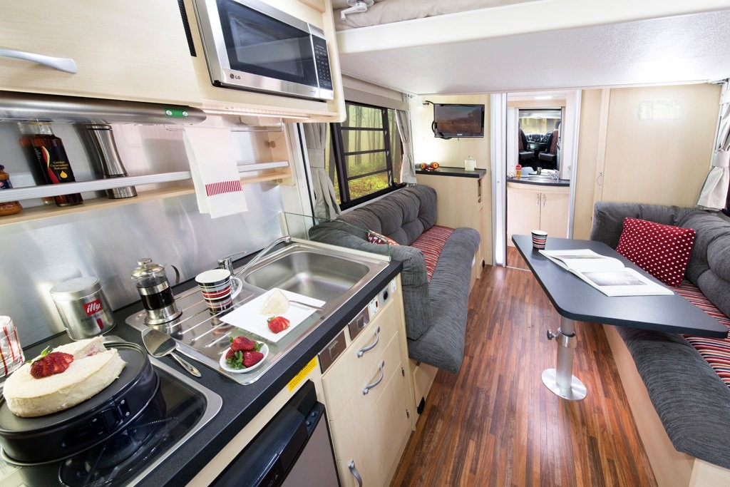 A view of the B6712 Avida Leura motorhome interior from toward the front of the vehicle to the rear with the electric roll down bed in a raised position. There are 13 colour collections available to the Leura, and the fabric colour scheme pictured is Scarlet Sunset.