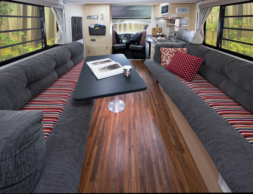 The lounge/dining area of the Avida B6712 Leura motorhome when the electric roll down bed is in the raised position. The colour scheme pictured is Scarlet Sunset.