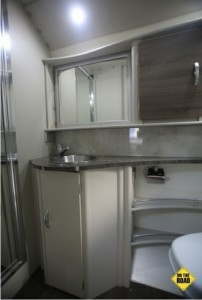 This ensuite has an elegantly curved vanity with a stainless steel sink, good storage cupboards and a shower with a handy moulded seat and shelves for soap. A full-length mirror on the outside of the shower door adds to a feeling of space.