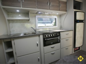 The fridge is an 184L AES three-way (12v, 240v and gas) and there's a microwave above while further forward you get a Thetford Mini Grill, rangehood, a stainless steel sink with drain board, cutlery drawer. Cupboards and drawers are CNC cut for a neat flush finish are built from durable and light poplar ply.