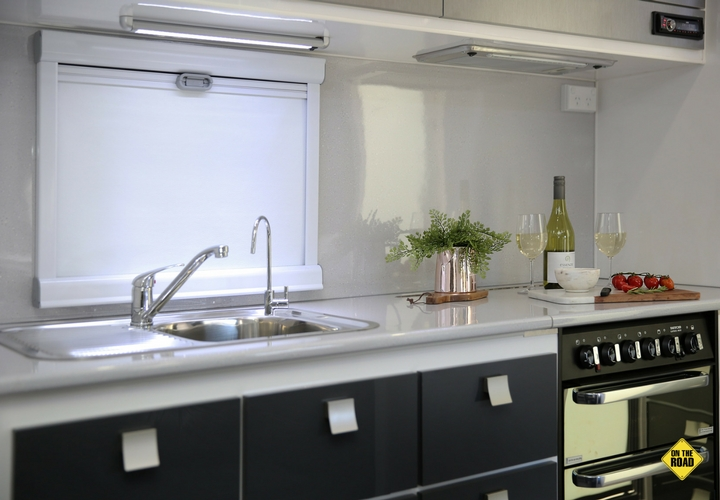 The driver side kitchen includes a three-tier pantry, an English made, full-size Thetford oven with cooktop and grill