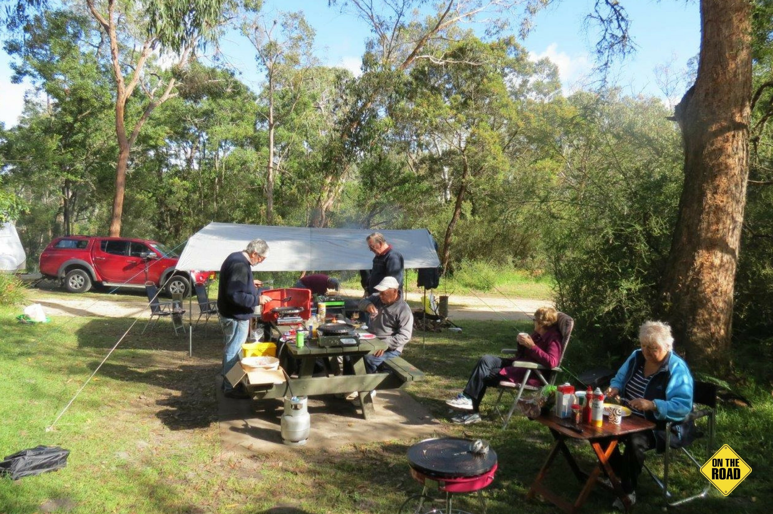 A happy group of campers preparing and tucking into a hearty bush breakfast.